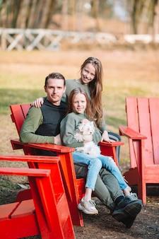 Padre e hijas lindas con perro al aire libre