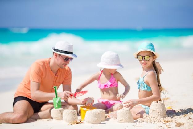 Padre e hijas pequeñas haciendo un castillo de arena en una playa tropical