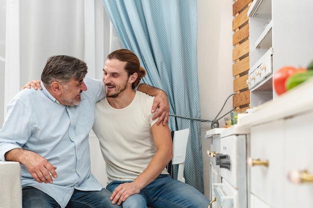 Padre e hijo abrazándose y hablando en la cocina