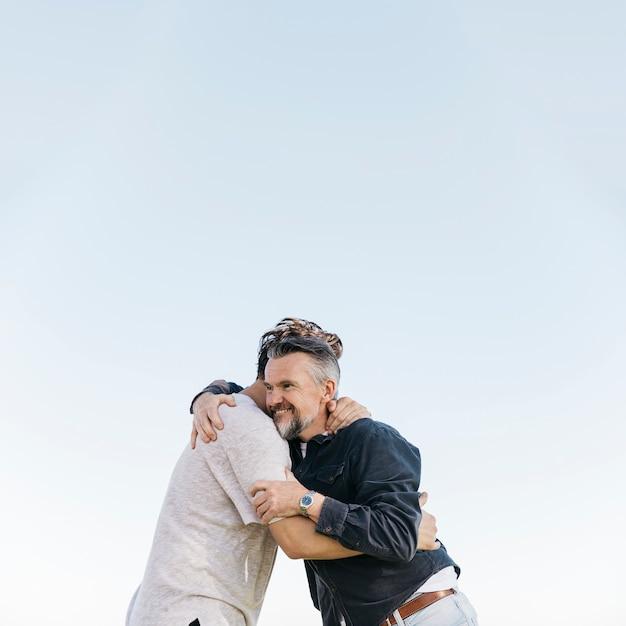 Padre e hijo abrazándose sobre fondo de cielo
