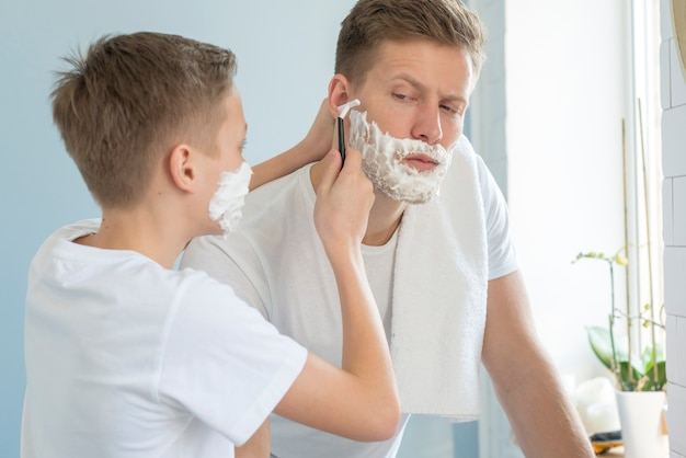 Padre e hijo se afeitan en el baño.