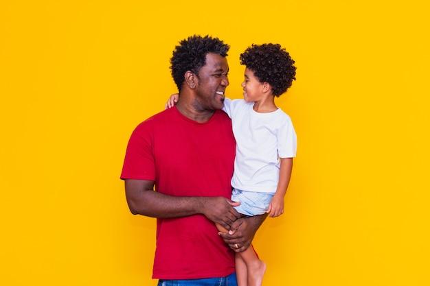 Padre e hijo afro sobre fondo amarillo sonriendo. concepto del día del padre