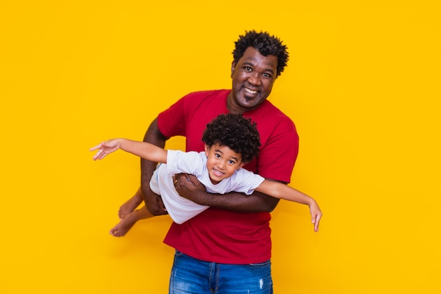 Padre e hijo afro sobre fondo amarillo sonriendo y jugando. concepto del día del padre