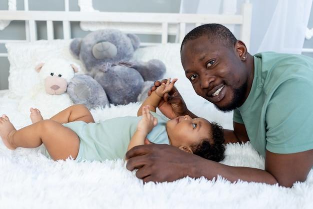 Padre e hijo afroamericanos se abrazan y juegan en casa en la cama, familia feliz