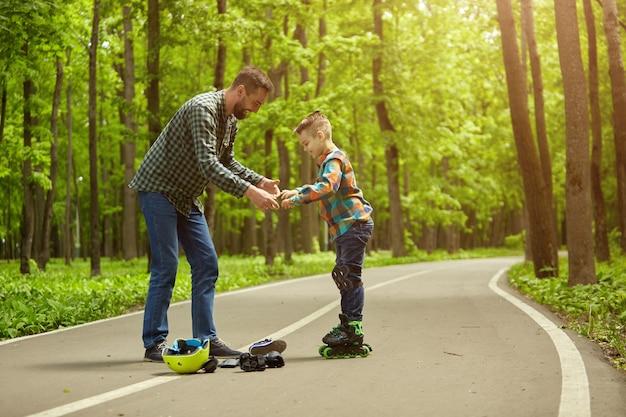 Padre e hijo al aire libre, preparándose para patinar