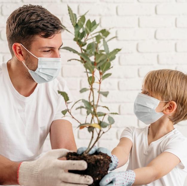 Padre e hijo aprenden a plantar juntos en casa mientras usan máscaras médicas