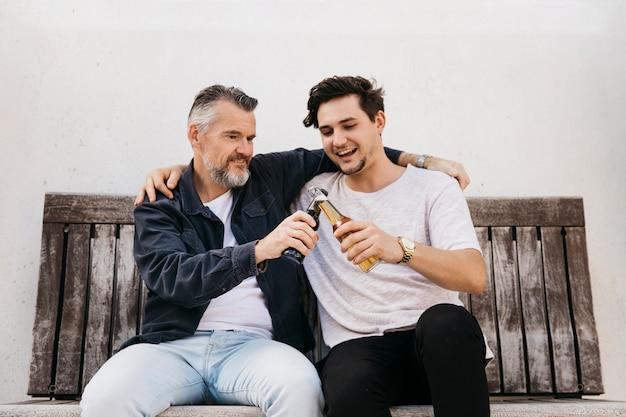 Padre e hijo en banco con cerveza