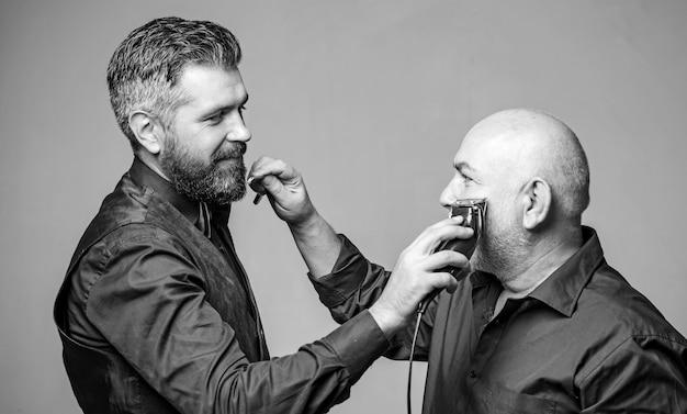 Padre e hijo barbudos. publicidad de peluquero. afeitarse el uno al otro. navaja y cuchilla eléctrica. hombre guapo