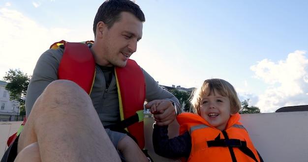 Padre e hijo en barco en chalecos salvavidas