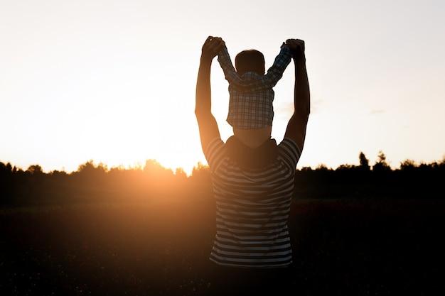 Padre e hijo caminando en el campo a la hora de la puesta del sol, muchacho sentado en los hombros de los hombres