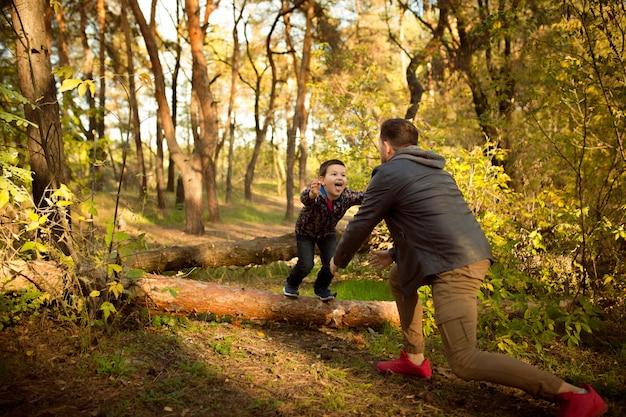 Padre e hijo caminando y divirtiéndose en el bosque otoñal, se ven felices y sinceros