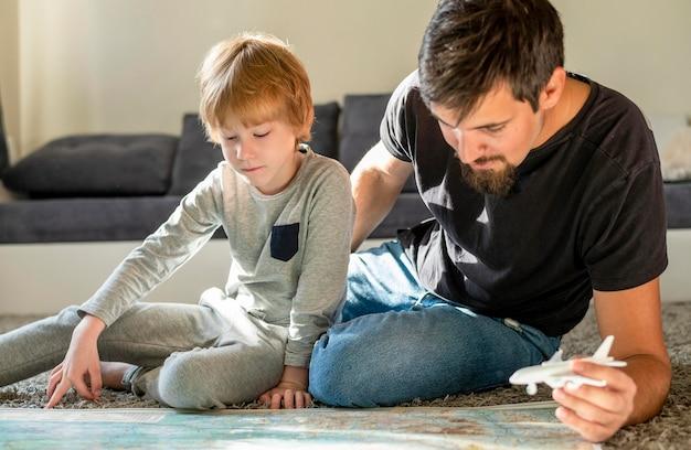 Padre e hijo en casa con figuras de mapa y avión