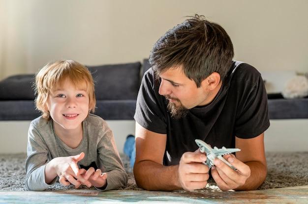 Padre e hijo en casa con mapa y figurilla de avión