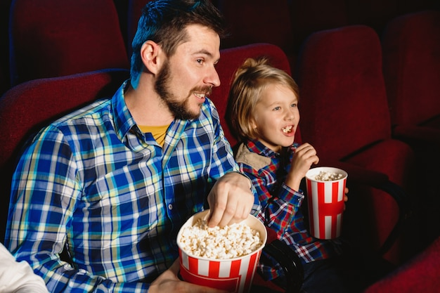 Padre e hijo caucásicos viendo una película en una sala de cine, casa o cine.