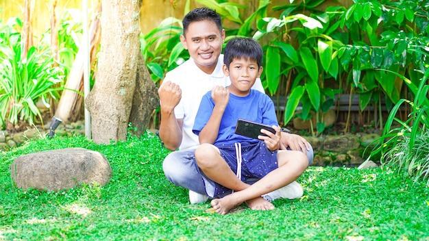 Padre e hijo celebran la felicidad en el jardín.