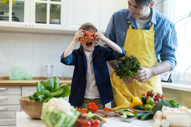 Padre e hijo cocinando ensalada