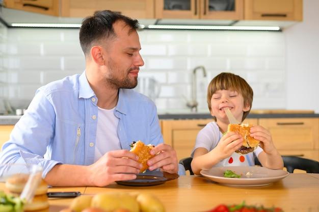 Padre e hijo comiendo deliciosas hamburguesas