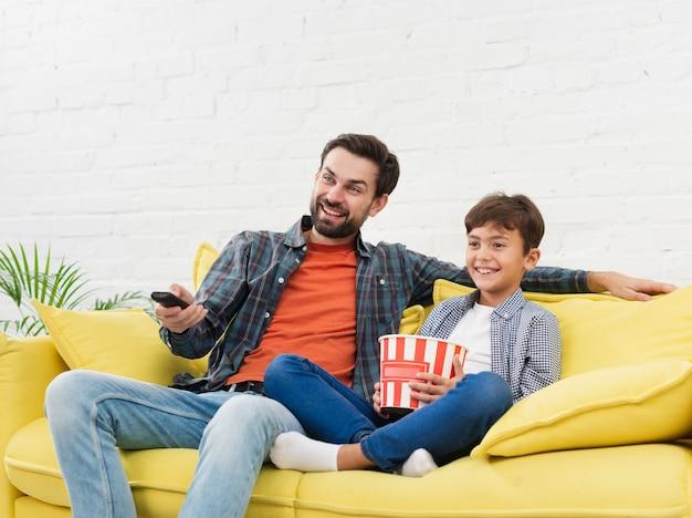 Padre e hijo comiendo palomitas de maíz y viendo televisión
