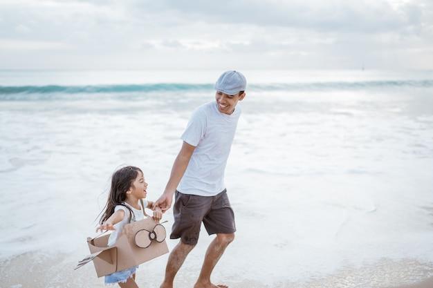 Padre e hijo corriendo con avión de cartón de juguete en la playa.