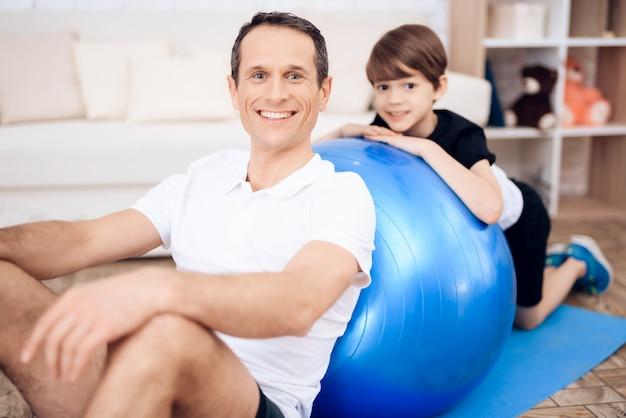 Padre e hijo se dedican al ejercicio físico junto con fitball.