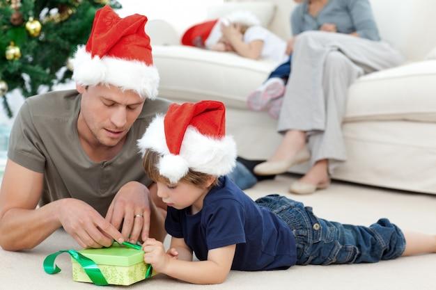 Padre e hijo, desenvolviendo un regalo tirado en el piso