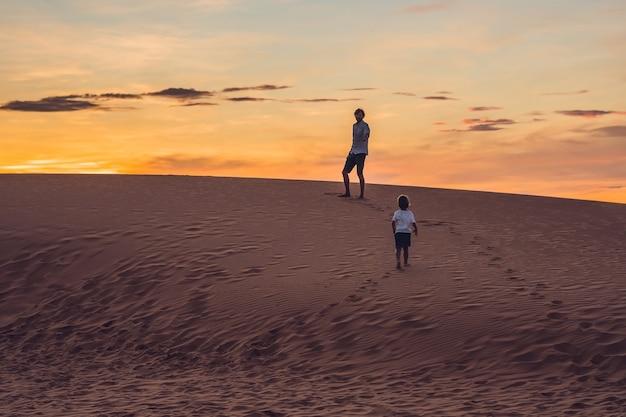 Padre e hijo en el desierto rojo al amanecer