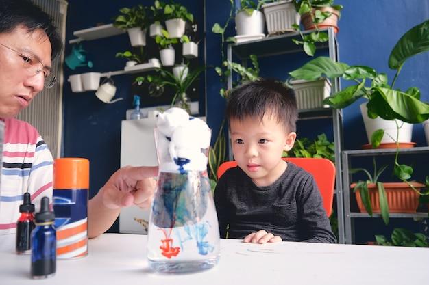 Padre e hijo se divierten haciendo un experimento científico fácil
