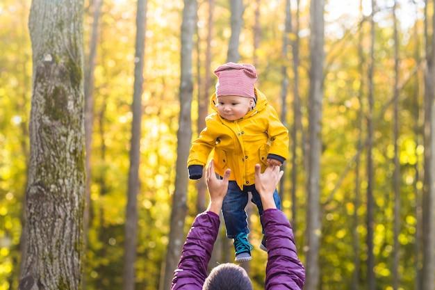 Padre e hijo divirtiéndose al aire libre en el bosque de otoño