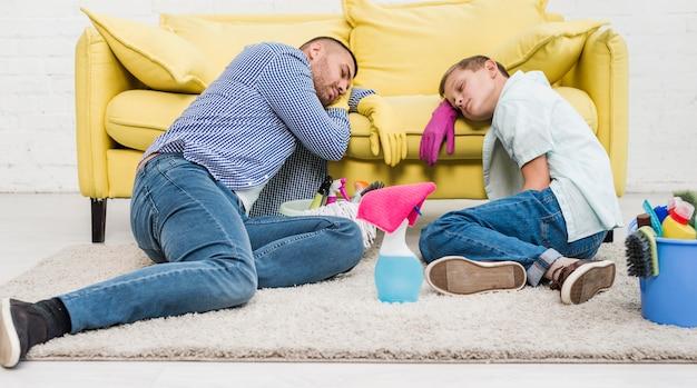 Padre e hijo durmiendo después de limpiar la casa