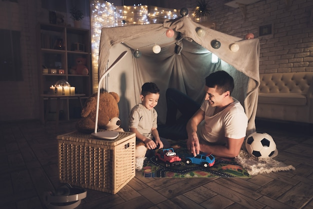 Padre e hijo están jugando con coches de juguete en la noche en casa.