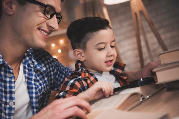 Padre e hijo están leyendo un libro de cuentos de hadas en la noche en casa