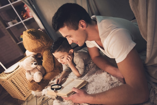 Padre e hijo están leyendo un libro por la noche.