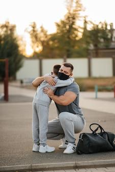 Padre e hijo están parados en el campo de deportes en máscaras después del entrenamiento durante la puesta de sol