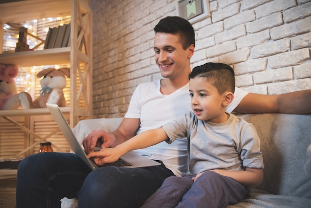 Padre e hijo están viendo películas en la computadora portátil por la noche.