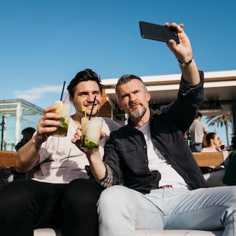 Padre e hijo haciendo selfie en bar
