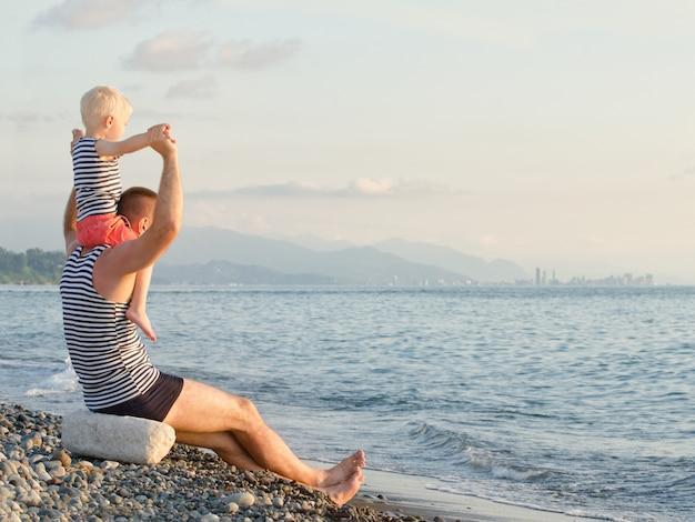 Padre e hijo en hombros con camisetas a rayas se sientan y miran el mar