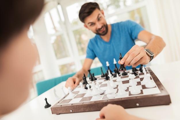 Padre e hijo juegan al ajedrez en su casa.