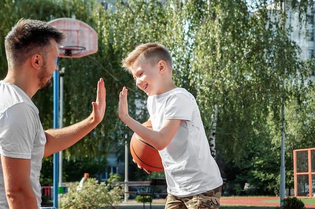 Padre e hijo juegan baloncesto juntos en la cancha de baloncesto