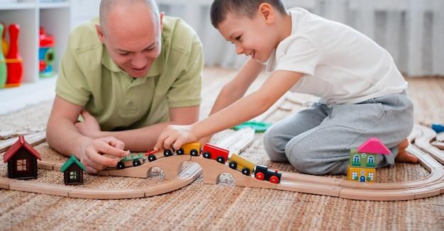 Padre e hijo juegan en un ferrocarril de madera de juguete en la sala de juegos.