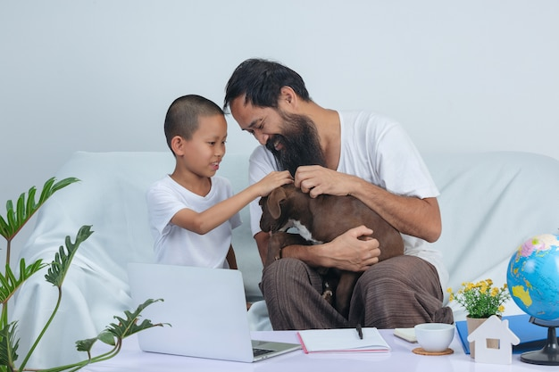 Padre e hijo juegan a un perro mientras trabajan en el sofá de casa.
