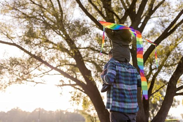 Padre e hijo jugando con una cometa desde atrás shot