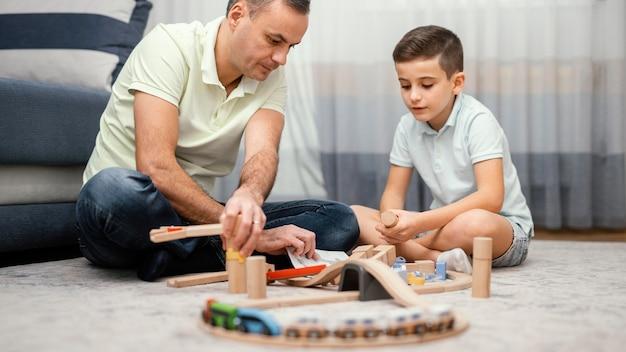 Padre e hijo jugando con juguetes en el dormitorio.