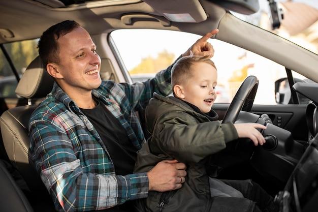 Padre e hijo jugando con la rueda del coche.