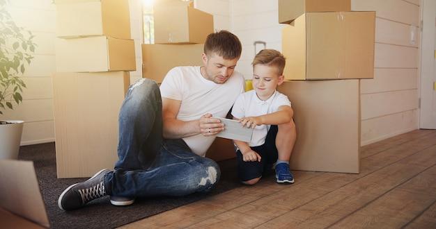 Padre e hijo jugando con tableta digital rodeada de cajas