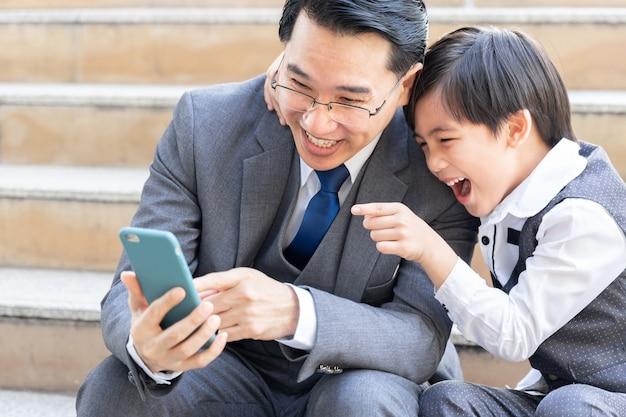 Padre e hijo jugando con teléfonos inteligentes juntos en el distrito de negocios urbano
