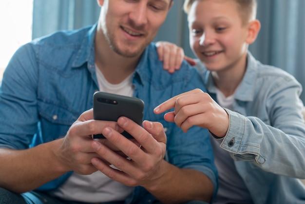 Padre e hijo lindo jugando en el teléfono
