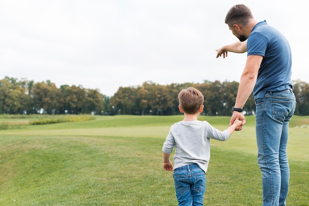 Padre e hijo, manos de valor en cartera, por detrás, tiro