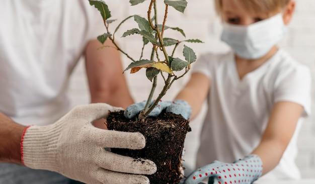 Padre e hijo con máscaras médicas y aprender a plantar