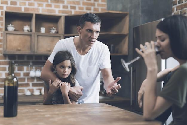 Padre e hijo miran a madre borracha en la cocina