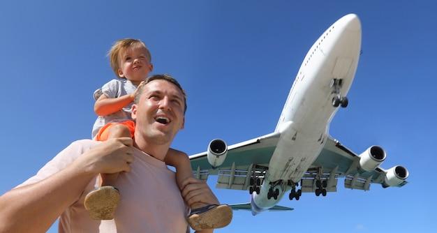 Padre e hijo mirando el avión de aterrizaje.